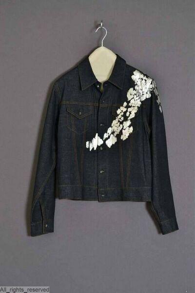 Jeans jas in donkerblauw denim met roestbruine siernaden; sluit met knopen gevormd door stukjes spiegel omwikkeld met wit metaaldraad; over de linker voorpand zilveren vlekken