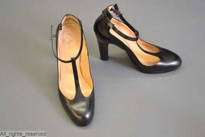 Schoenen met ronde tip en hoge hakken in zwart leder; sluit met gesp en enkelband