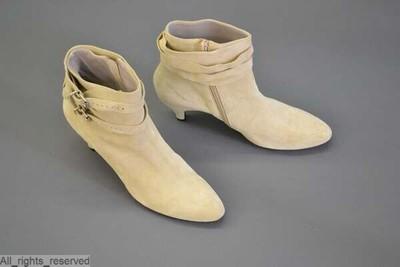 Laarzen met ronde tip en hoge, puntige hakken in beige zeemleder; over de enkel een band met gespen