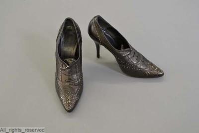 Schoenen met puntige tip en hoge naaldhakken in zwart leder versierd met perforaties en metalen stiften