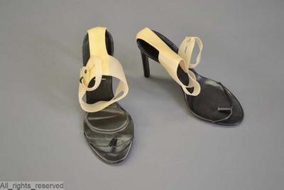 paar schoenen met puntige tippen en hoge hakken in zwart leder met over tenen zwart bandje; over de enkel een band in beige kunststof verbonden met de hiel met een strook beige leder
