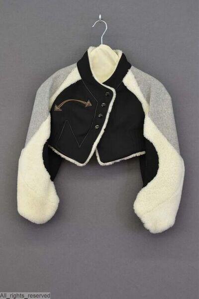 Korte jas, bolero, met lange mouwen en rechtopstaande kraag. Het lijf is uitgevoerd in een zwarte wollen stof, vooraan gevoerd met wit omgekeerd schapenbont, achteraan met zwarte kunstzijde. De mouwen zijn gemaakt deels...