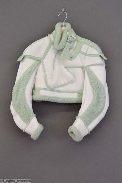 Korte witte jas, bombardier, in kunstvezel, met lange mouwen en rechtopstaande kraag, volledig gevoerd met lichtgroen geverfd schapenbont. In de mouwen zijn stukken van hetzelfde lichtgroene bont gezet. De jas is bijkomend...