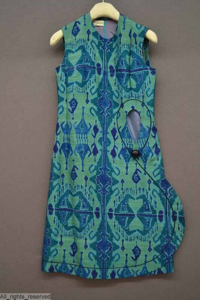 Mouwloze jurk met ronde hals in groene shantung bedrukt met een op Centraal-Aziatische ikats gïnspireerd motief in vlauw en rok heeft een gebogen opening met grote zwarte kunststof knoop; voering in blauwgrijze zijde
