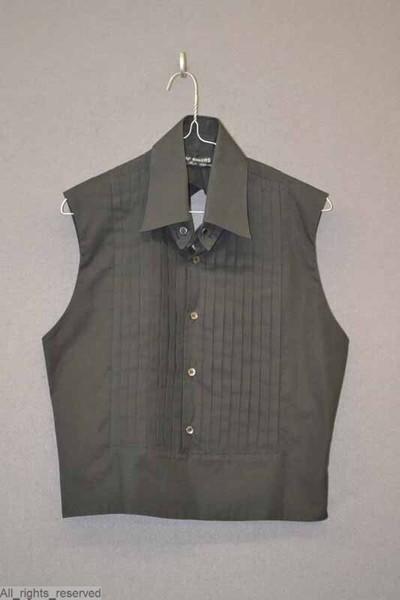 Zwart katoenen hemd met losse puntkraag, zonder mouwen en met een open rug. De kraag wordt op het hemd vastgemaakt met een knoop middenachter en met twee losse metalen knopen vooraan. Het borststuk is versierd met platte...