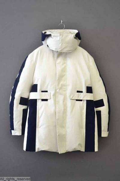 Halflange witte katoenen jas, parka, met rechte opgezette kraag en kap, en met twee steekzakken vooraan. De jas heeft midden op de rug, bovenop de armen, vooraan, en op de zijkanten stroken in donkerblauwe klittenband. De...