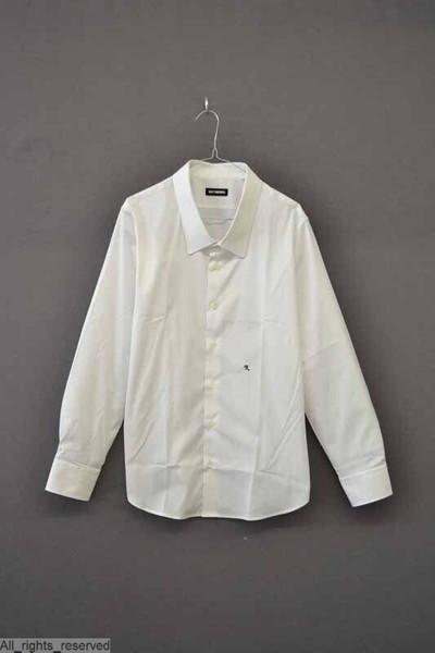 Wit katoenen hemd, met een opgezette oversized puntkraag, lange mouwen met manchetten en een sluiting met knopen middenvoor. Links op de buik is de letter R geborduurd in donkerblauw garen.