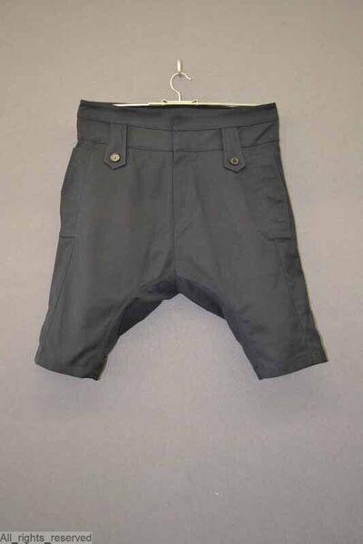 A: Marineblauwe korte broek, shorts, met twee verticale steekzakken opzij vooraan en twee klepzakken op het zitvlak.  B: Onder de broekband bevinden voor- en achteraan telkens twee litsen waar een brede ceintuur doorheen...