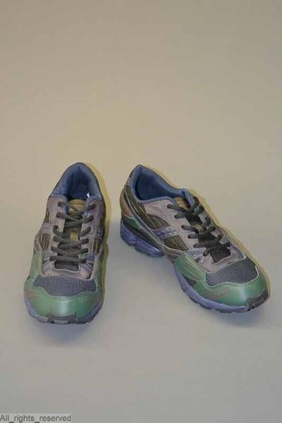 Paar schoenen, trainers, in zwarte en donkergrijze kunstvezel, met een tip en deel van de hiel in donkergroene kunststof, imitatieleder, en met een zool in donkerblauwe kunststof en zwarte onderkant met reliëf. De schoen...
