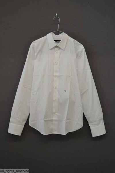 Wit katoenen hemd, met een opgezette puntkraag, lange mouwen met manchetten en een sluiting met knopen middenvoor. Links op de buik is de letter R geborduurd in donkerblauw garen.