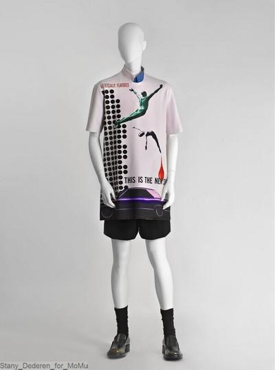 Hemd in katoen met opgezette puntkraag en korte mouwen, bestaande uit aan elkaar gestikte verticale panden in zwart, roze, blauw, groen en wit; sluiting middenvoor met knopen.