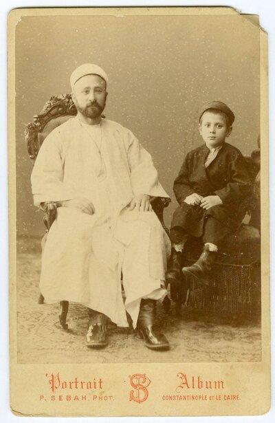 Φωτογραφία άνδρα με οθωμανική ενδυμασία και μικρό παιδί σε φωτογραφ είο της Κωνσταντινούπολης