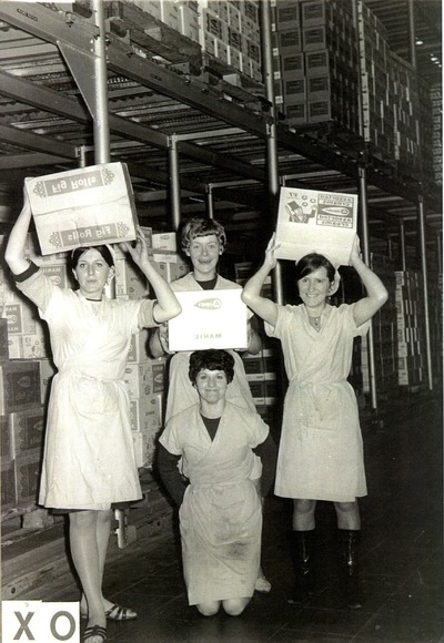 Female factory workers holding up boxes of products | Jacob's Biscuit Factory