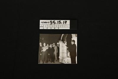 95.15.17.jpg - φωτογραφία - φωτογραφία ασπρόμαυρη που απεικονίζει επτά άνδρες που τραγουδούν όρθιοι, δίπλα σε ένα ομοίωμα αψίδας, πιθανόν του Γαλερίου. Οι δύο παίζουν κιθάρα