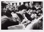 Foto van Ed van der Elsken, voorstellende diverse met stokjes etende mensen