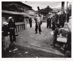 Foto van Ed van der Elsken, voorstellende een straatbeeld met een man met een bunraku-pop en publiek