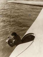 Luchtfotografie. Man hangt uit vliegtuig om luchtfoto's te maken boven water. Plaats en land onbekend, 1940.