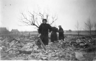 Serooskerke. Jan Berrevoets met twee dochters bij de puinhopen van hun huis in Serooskerke.