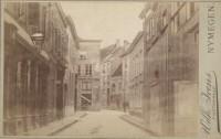 Midden op de achtergrond het begin van de Pauwelstraat. Rechts daarvan (bij de twee personen) de hoek met de Korte Molenstraat en links in het midden voor het winkelpand het begin van de Broerstraat