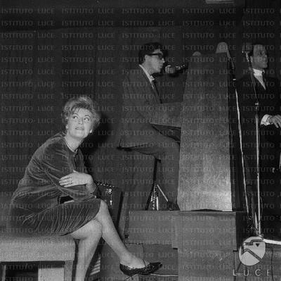 Peppino Di Capri canta in piedi suonando la pianola; Lilly Lembo ascolta seduta su uno sgabello