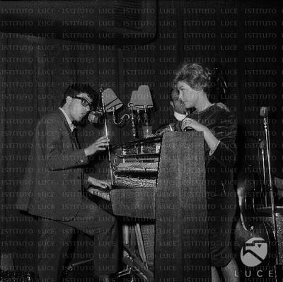 Peppino di Capri in piedi suona la pianola, Lilly Lembo lo ascolta