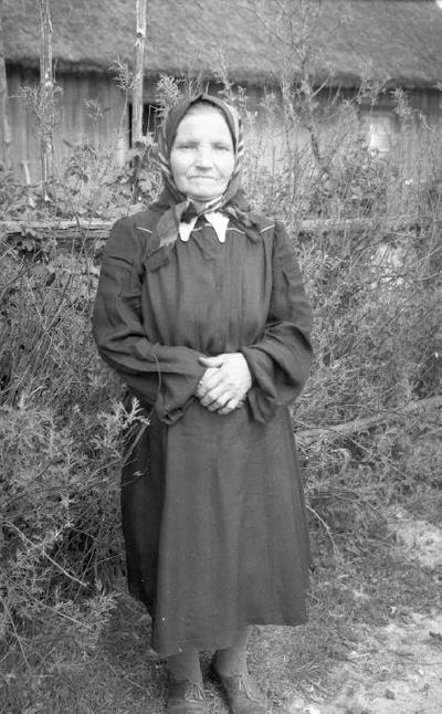 Image from object titled Siužetinė. Senyva moteris su skarele, rankas sudėjusi ant pilvo. Tolumoje pastatas šiaudiniu stogu.