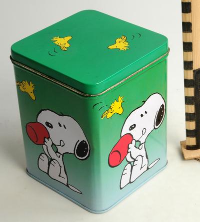 Vierkante groene trommel met op de zijden 4 afbeeldingen van Snoopy met een beker, op de bodem Peanuts characters, 1958-1961