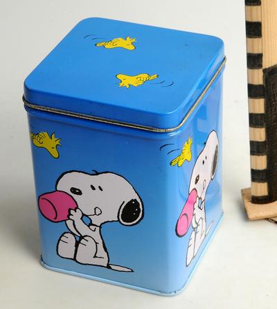 Vierkante blauwe trommel met op de zijden 4 afbeeldingen van Snoopy met een beker, op de bodem Peanuts characters, 1958-1961