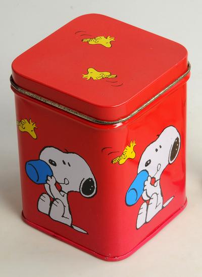 Vierkante rode trommel met op de zijden 4 afbeeldingen van Snoopy met een beker, op de bodem Peanuts characters, 1958-1961