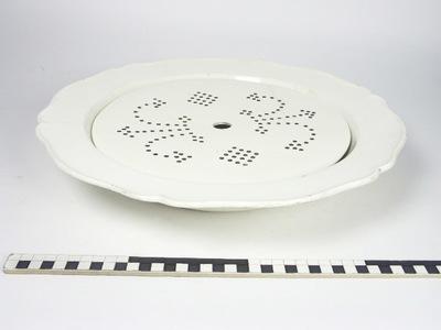 Grote schotel met binnenschotel waarin gaatjes van creme aardewerk