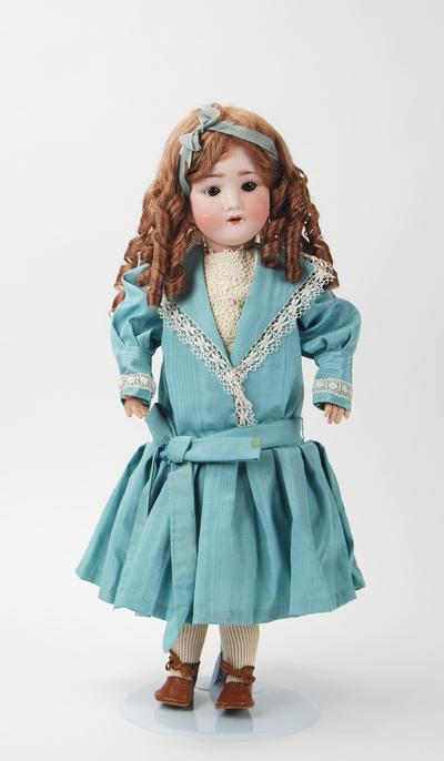 Pop met pijpenkrullen, blauw jurkje en bruine schoentjes
