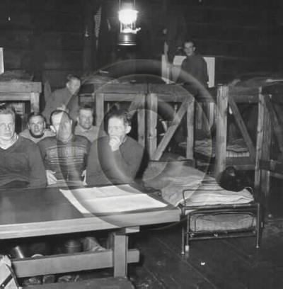Image from object titled Enso-Gutzeit Osakeyhtiön Mularin kämppä. Miehet istuvat penkeillä pöytien ääressä illanvietossa. Pöydälle on levitetty kartta. Seinustoilla kerrossängyt, keskellä heteka ja katosta roikkuu karbidilamppu.