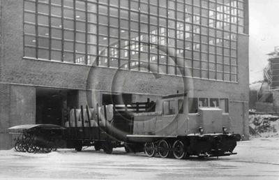 Image from object titled Paperirullia siirretään junalla Enso-Gutzeitin Kotkan voimapaperitehtaalla. Tehtaan seinän vieressä polkupyöräkatos.