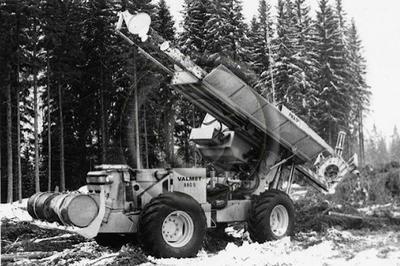 """""""Pika 50"""" (alkuperäinen kuvateksti). Sakari Pinomäen kehittämä prosessori hakkuuaukealla Harvialan kuusikkomaisemissa. Peruskoneena Valmet 880 S -metsätraktori."""