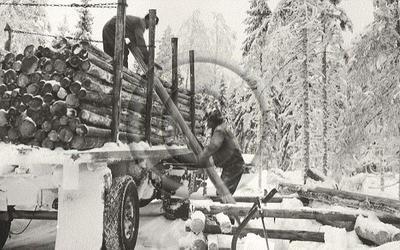 """Miehet lastaavat kuorittua puutavaraa auton kyytiin. """"Palstalta kuormausta Hirvasselän työmaalla."""" (alkuperäinen teksti)."""