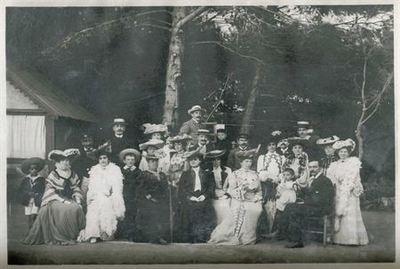Retrato de grupo ao ar livre. Grupo composto por várias figuras femininas e masculinas, incluindo algumas crianças. Estão dispostas em duas filas, estando na primeira, sentadas, sete figuras e na segunda, em seu redor, as...