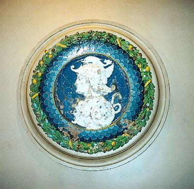 Medalhão com a representação de um busto de guerreiro retratado de perfil, envolto por um cordão amarelo, uma cercadura interna de escamas em vários tons de azul, e uma cercadura externa composta de folhas de louro,...