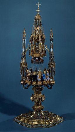 Custódia em ouro assente numa base oblonga polilobolada sobre a qual se repartem seis reservas molduradas por cordões de esmalte azul e preenchidas em relevo por flores, frutos, moluscos e aves exóticas em diversas...