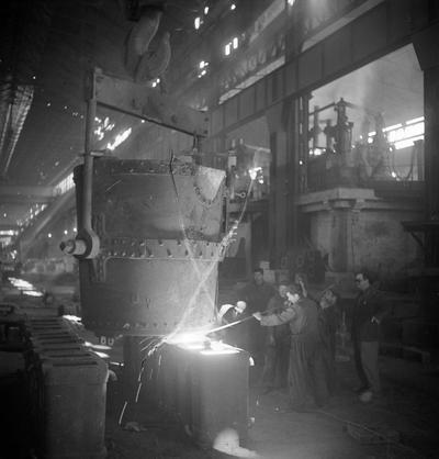 Image from object titled Fábrica de Fundiciones y hornos de fundición en Reinosa [Máquina con operarios llenando moldes con material fundido]