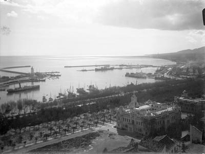 Málaga. Hafen von oben [El Puerto visto desde arriba. Tomada en las faldas del monte Gibralfaro. Obras de la construcción de la casa consistorial llamada Casona del Parque. Al fondo, la sierra de Mijas]