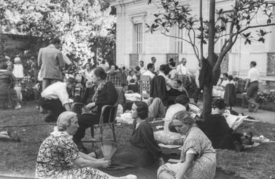 [Grupo de personas, algunas sentadas y otras tumbadas, en los jardines de la Embajada Alemana de Madrid tras ser evacuados por el estallido de la Guerra Civil]