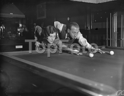 Billiards at the Burwat Hall  , Soho Square . Miss Joyce Gardner , The ladies professional billiards champion , with her fiance , Mr A R Williams  27 December 1933