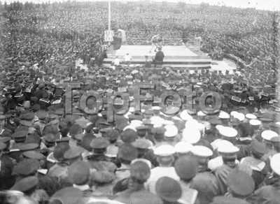 Image from object titled 1916 Finals of the Grand Fleet boxing competitions held on the island of Flotta, by Scapa Flow, where the Grand Fleet was then stationed. The boxing ring was jury-built from spars, ropes, canvas and planking scavenged from various ships by a couple of enterprising Chief Petty Officers, names now not known.