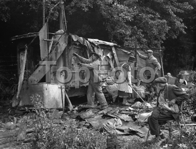 An old man watches on as a shack in Kingsdown is demolished . 1936