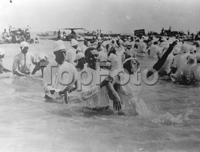 """Original caption: [ Sing """"Hallelujah""""! An enthusiastic candidate, under strong emotional stress, as with 200 others, was baptised by Bishop Grace, Negro Evangelist of the House of Prayer at Newport News, Virginia. The..."""
