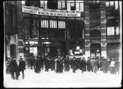 Image from object titled 18-4-13, grève générale en Belgique [un rassemblement devant un local syndical, une grande banderole d'appel à la grève pacifique accrochée à la façade] : [photographie de presse] / [Agence Rol]