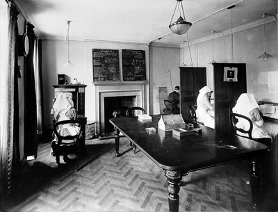 Image from object titled Ambulance Column depot, 9 Gower Street, London: the Telephone Room, with officials in telephone booths, perhaps answering enquiries. Photograph, September 1918.