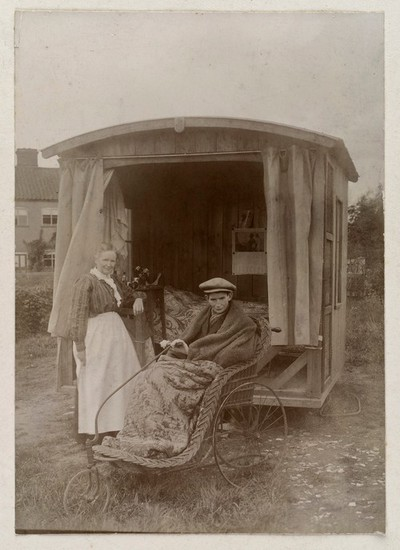 Image from object titled An invalid boy in a Bath chair outside an open air