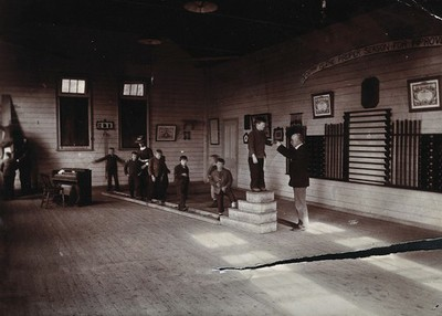Image from object titled Metropolitan Lunatic Asylum, Kew, Victoria, Australia: boys walking along a ladder laid upon the floor. Photograph.