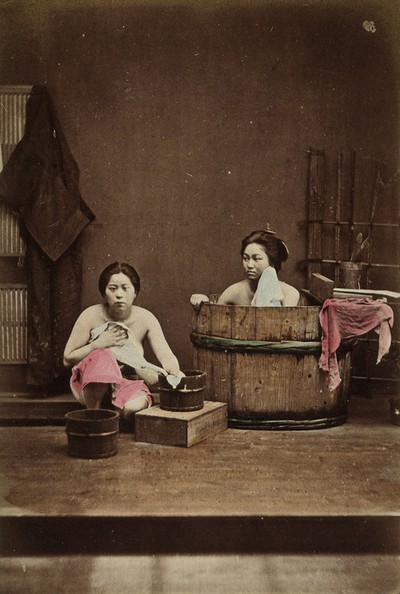 Image from object titled Japan: two women washing: one bathing in a wooden tub and one squatting down holding a flannel. Coloured photograph, 1870/1890.